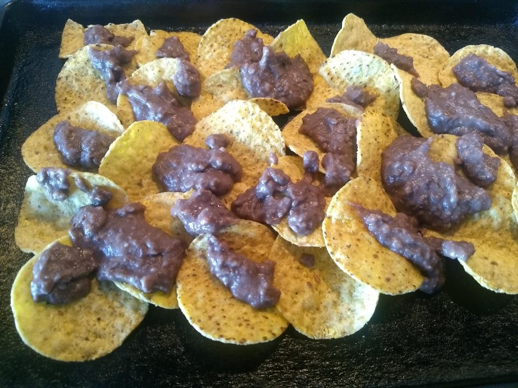 refried beans on nacho chips